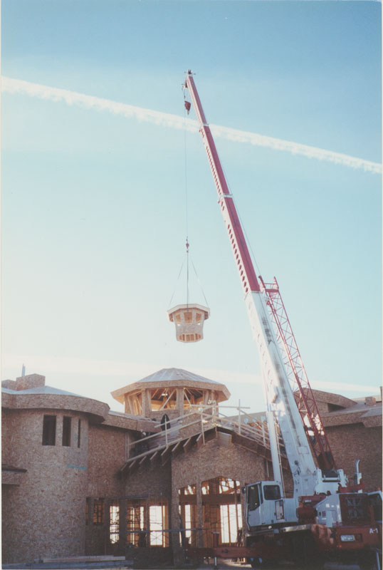 photo shows a crane lifting the cupola into place during the construction of centre 2000