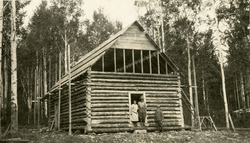 Herman and Catherine Klukas stand in the doorway of a partially built log cabin. An unnamed man stands in front of the cabin to their left