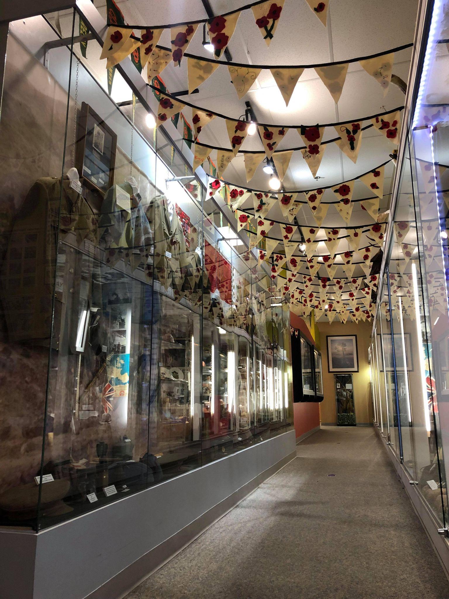 Poppy bunting hangs in a corridor of military regalia