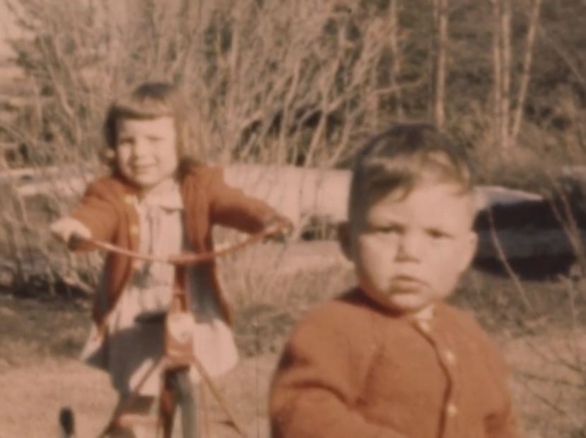 A still from the film that shows a smiling young child on a bicycle with another child in the foreground
